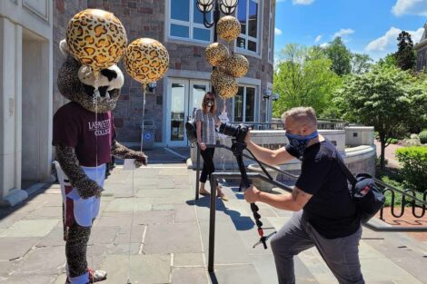 photographer points camera at Leopard mascot holding balloons